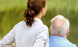 A senior and a caregiver looking out to a green field