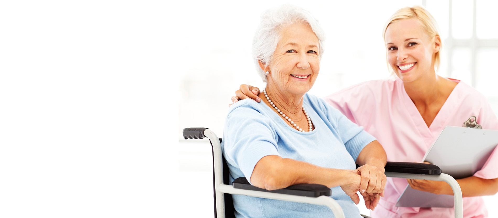 A smiling elderly woman with a smiling caregiver