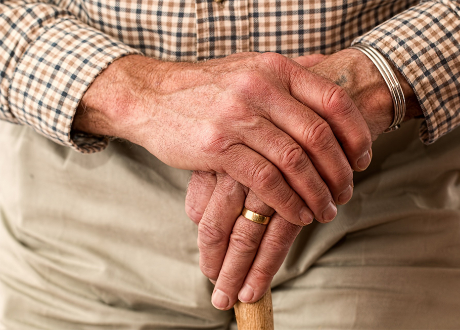 A senior holding his other hand